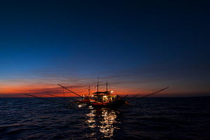 A fishing boat using a kerosine lamp to illuminate the sea from dusk to dawn. The light attracts the fishermen's target fish, anchovies and silversides. Philippines, March 2010. - Jurgen Freund