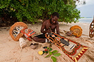 Papua New Guinean artist carving Malagan wooden sculptures, the ceremonial art of New Ireland's living culture, from the soft, abundant Saba tree wood. He uses four natural pigments for paint.  Kavien...  -  Jurgen Freund