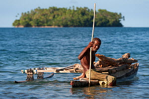 Old man of the of M'buke community gathering firewood for his home in a small traditional outrigger canoe. New Ireland, Papua New Guinea, June 2010. - Jurgen Freund