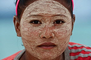 A young Bajau woman with burak (face makeup), a paste made from pounded rice and tumeric which also serves as a natural sunblock. Wearing burak signifies the young lady is single and available for mar... - Jurgen Freund