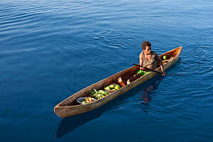 Papua New Guinean islander paddling his dugout canoe to trade fresh vegetables. He will come back with instant noodles, rice, soap and other groceries he would normally have no access to. Papua New Gu... - Jurgen Freund