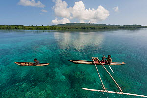 Papua New Guinean islanders paddling their dugout canoes to trade fresh vegetables. They will come back with instant noodles, rice, soap and other groceries they would normally have no access to. Papu... - Jurgen Freund