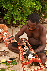 Papua New Guinean artist carving Malagan wooden sculptures, the ceremonial art of New Ireland's living culture, from the soft, abundant Saba tree wood. He uses four natural pigments for paint. Kavieng...  -  Jurgen Freund