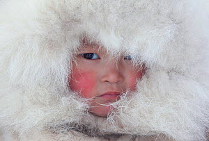 Nenya Vanuito, a young Nenets girl, wearing a traditional hat with fur trim at a winter camp near Tambey. Yamal Peninsula, Western Siberia, Russia. March 2011 - Bryan and Cherry Alexander