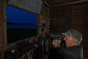 Volunteer Warden, Ray Sykes, using night vision optics to observe the Manton Bay osprey pair at night, Rutland Water, Rutland, UK, April 2011. During the incubation period the Osprey nest is observed...  -  Terry Whittaker / 2020VISION