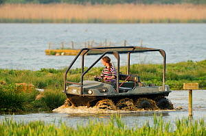 Assistant Warden Lloyd Park checks nesting islands and rafts at the Anglian Birdwatching Centre using an amphibious vehicle, Rutland Water, Rutland, UK, April 2011, Model released  -  Terry Whittaker / 2020VISION