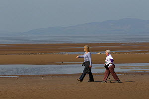 Two women walking along sandy beach at low tide, near Maryport, Solway Firth, Cumbria,UK, April 2011 - Peter Cairns / 2020VISION