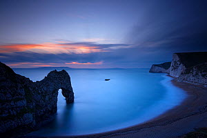 Durdle Door and the Jurassic Coast at dusk, with Weymouth Bay and Portland beyond. Dorset, England, November 2010. - David Noton