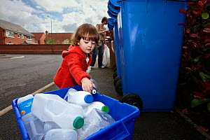 Young girl and mother recycling plastic and cardboard in street, Derbyshire, UK, April, Model released  -  Chris O'Reilly