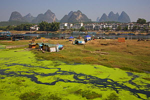 Polluted tributary of the Li River with town and mountains on the horizon. Yangshuo, Guangxi, China, November 2006. - Florian Möllers