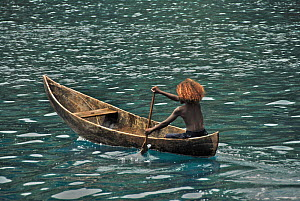 Young girl paddling dugout canoe, Peava village, Solomon Islands, Melanesia, September 2008.  -  Fred Olivier