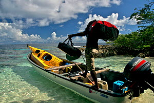 Man loading demountable kayak into banana boat, Solomon Islands, Melanesia, November 2008. - Fred Olivier