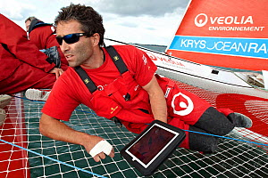 Crew member using hand held navigational device on board MOD 70 trimaran 'Veolia Environnement' during the Krys Match, La Trinite-sur-Mer, Brittany, France, October 2011. All non-editorial uses must b... - Benoit Stichelbaut