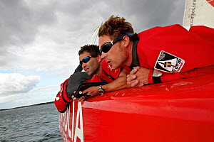 Crew members using hand held navigational device on board MOD 70 trimaran 'Veolia Environnement' during the Krys Match, La Trinite-sur-Mer, Brittany, France, October 2011. All non-editorial uses must...  -  Benoit Stichelbaut