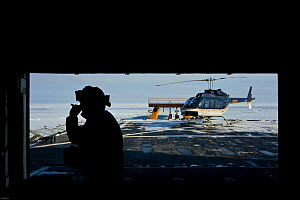 Helicopter and crew on deck of US Coastgaurd ship 'Healy' in frozen Bering Sea, Alaska, March 2008. Taken on location for the BBC series, Frozen Planet.  -  Jeff Wilson