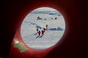 View through the porthole of science teams and Frozen Planet film crew working on the sea ice in the Bering Sea, Alaska, USA, March 2008. The film crew were in search of Spectacled eider ducks, temper...  -  Jeff Wilson