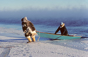 Inuit hunters hauling boat out of the water after seal hunting at the floe edge in frost smoke. Igloolik, Nunavut, Canada, 1990. 40 BELOW bookplate. - Bryan and Cherry Alexander