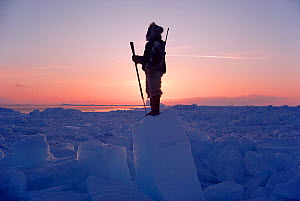 Inuit hunter scanning ice of Melville Bay for Polar bears. Northwest Greenland, 1986. 40 BELOW bookplate. - Bryan and Cherry Alexander
