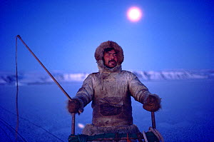 Inuit hunter travelling by dog sled during the polar night. Northwest Greenland, 1987. 40 BELOW bookplate. - Bryan and Cherry Alexander