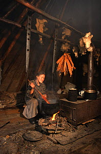 Nenets woman cooking fish inside her tent at summer fishing camp. Yamal, Western Siberia, Russia, 2000. 40 BELOW bookplate. - Bryan and Cherry Alexander