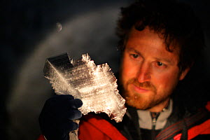 BBC producer Chadden Hunter looking at the incredible ice crystal formations inside volcanic ice caves below Mount Erebus, Antarctica. Taken on location for BBC Frozen Planet series, 2009  -  Chadden Hunter