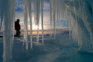 Person standing infront of long icicles, outside volcanic ice cave, Mount Erebus, Antarctica. Taken on location for BBC Frozen Planet series, 2009  -  Chadden Hunter
