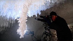 Cameraman Gavin Thurston filming ice crystals under volcanic ice cave, Mount Erebus, Antarctica. Taken on location for BBC Frozen Planet series, 2009  -  Chadden Hunter