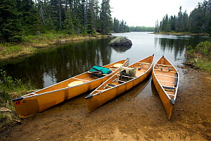 Three canoes pulled up on the shore in the Boundary Waters Canoe Area Wilderness, Minnesota, USA, May 2010 - Kirkendall-Spring