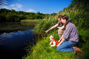 Family sitting beside water watching wildlife at Westhay SWT reserve, Somerset Levels, Somerset, England, UK, June 2011 Model released  -  Guy Edwardes / 2020VISION