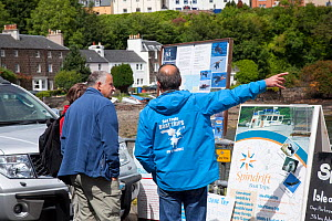 Boat operator touting for business with photographs of introduced Sea eagles, Portree, Skye, Inner Hebrides, Scotland, UK, June 2011  -  Peter Cairns / 2020VISION