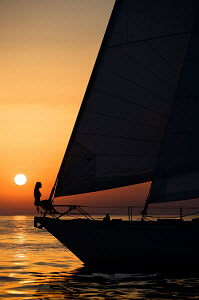 Woman silhouetted on bow of cruising yacht 'Pegasus' at sunset near to Portoroz, Slovenia, July 2007. For editorial use only. - Sea & See