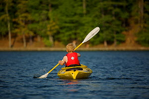 Rear view of a 6 year boy kayaking on Walden Pond, Massachusetts, USA, model released, May 2007 - Tim Laman