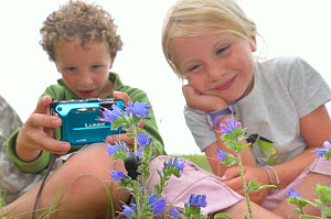 Children in garden photographing flowers and insects. France, Europe, August. Model released.  -  Dan Burton