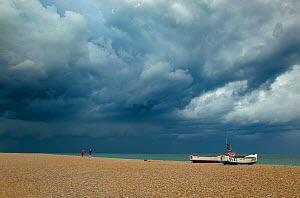 Two people walking on Cley beach near boats looking towards Blakeney Point with storm clouds overhead, Norfolk, UK, July 2011  -  Ernie Janes