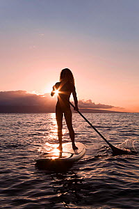 Surf instructor Tara Angioletti at sunset on a stand-up paddle board off Canoe Bearch, Maui, Hawaii. Model released. - David Fleetham