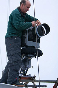 Cameraman, Doug Allan, fixing stabilised high definition film camera on the 'Golden Fleece' (base ship of the BBC film crew) as it passes along the  Antarctic Peninsula, Antarctica, January 2009, Take... - Kathryn Jeffs