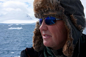 Doug Allan, cameraman, looking for Killer whales (Orcinus orca) in Antarctica.  Taken on location for BBC Frozen Planet series, January 2009  -  Kathryn Jeffs