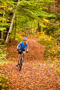 Woman mountain biking on a trail in an abandoned granite quarry on Millstone Hill, Barre, Vermont, USA. autumn. Model released, October 2010  -  Jerry Monkman