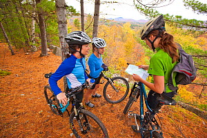 Three women check their map while mountain biking on a trail in an abandoned granite quarry on Millstone Hill, Barre, Vermont, USA. Model released, October 2010  -  Jerry Monkman