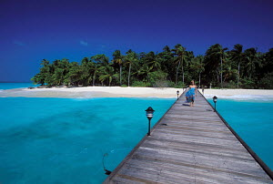 Woman walking across jetty from Palm Beach Island Resort, Maldives. - Sea & See
