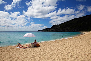 Couple sunbathing on beach, Saint Barthelemy, Caribbean, December 2011. - Benoit Stichelbaut