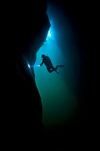 Scuba diver exploring a sea cave beneath Giants Legs, Bressay, Shetland Islands, Scotland, UK - Alex Mustard / 2020VISION