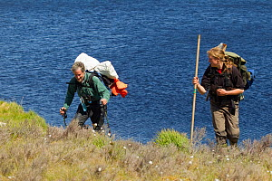 Two RSPB scientists carrying equipment for the study of aquatic invertebrate adundance as part of Common Scoter (Melanitta nigra) research, Forsinard Flows RSPB reserve, Flow Country, Sutherland, High...  -  Mark Hamblin / 2020VISION
