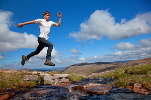 Boy (aged 17) jumping across upland stream, Cairngorms National Park, Highlands, Scotland, UK, August, Model released  -  Mark Hamblin / 2020VISION
