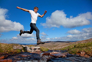 Boy (aged 17) jumping across upland stream, Cairngorms National Park, Highlands, Scotland, UK, August, Model released. 2020VISION Exhibition. 2020VISION Book Plate. Did you know? More than a million p...  -  Mark Hamblin / 2020VISION