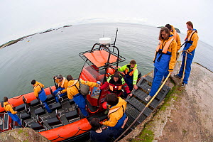 Group of tourists wearing waterproof clothing and life jackets board zodiac boat for tour around Bass Rock, North Berwick, Firth of Forth, Lothian, Scotland, UK, August 2011 - Peter Cairns / 2020VISION