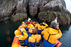 Group of tourists wearing waterproof clothing and life jackets photograph seabirds from zodiac boat on tour around Bass Rock, North Berwick, Firth of Forth, Lothian, Scotland, UK, August 2011  -  Peter Cairns / 2020VISION