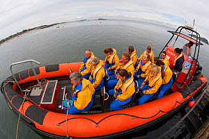 Group of tourists wearing waterproof clothing and life jackets in zodiac boat for seabird safari tour around Bass Rock, North Berwick, Firth of Forth, Lothian, Scotland, UK, August 2011  -  Peter Cairns / 2020VISION