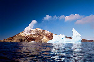 Iceberg floating in front of smoking volcano. Zavadovski Island, South Sandwich group, Antarctica. Freeze Frame book plate page 153.  -  Doug Allan