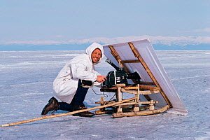Cameraman Doug Allan filming seals with white sail for camouflage, Lake Baikal, Siberia, Russia, April 1989. Freeze Frame book plate page, 48.  -  Doug Allan